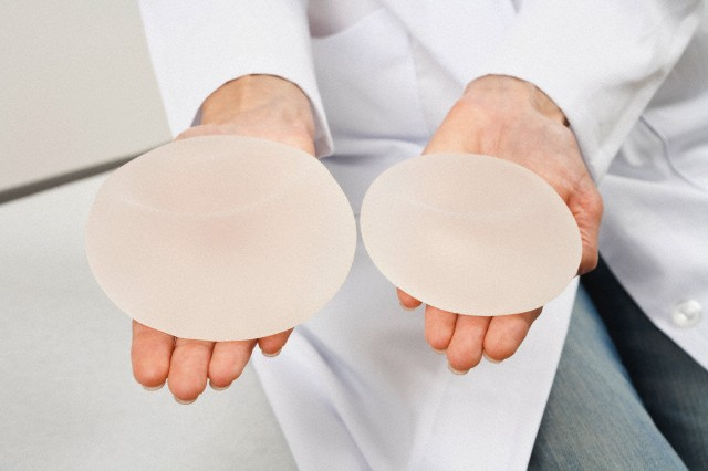 Germany, Munich, Doctor holding breast implant, close up